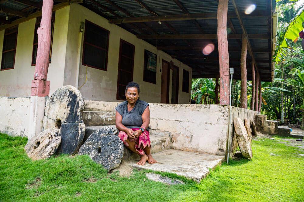 Yap island, Micronesia - Local Micronesian woman sitting on the porch alongside three rai stones. Photo: maloff/Shutterstock.com