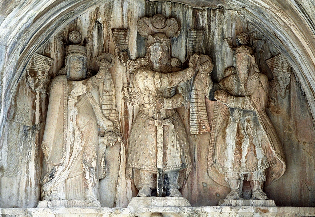 Taq-e Bostan high-relief of the investiture of Khosrow II (r. 590 to 628). The king (center) receives the ring of kingship from Mithra (right). On the left, apparently sanctifying the investiture, stands a female figure generally assumed to be Anahita.