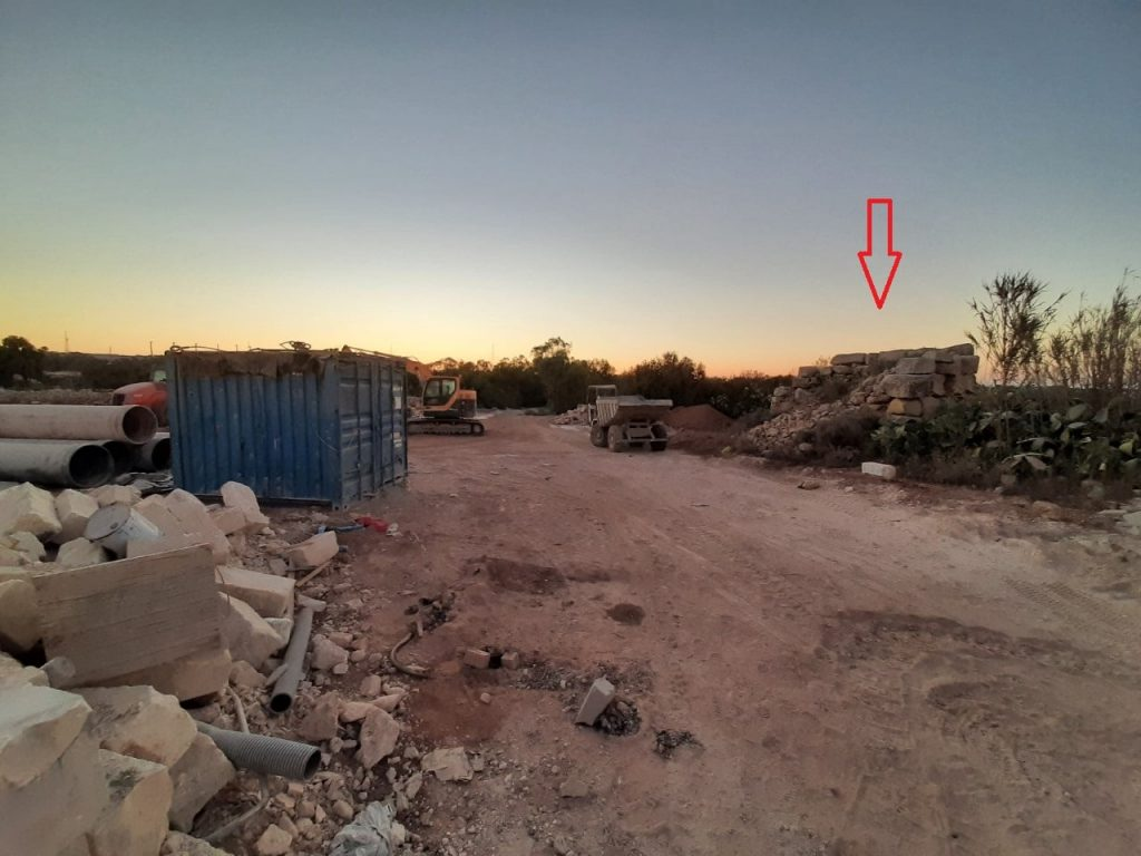 Photograph shows field adjacent to Tal-Wilġa ancient building levelled; it is used for storage, park heavy machinery and to deposit rubbish (Tal-Wilġa ancient building marked with an arrow).