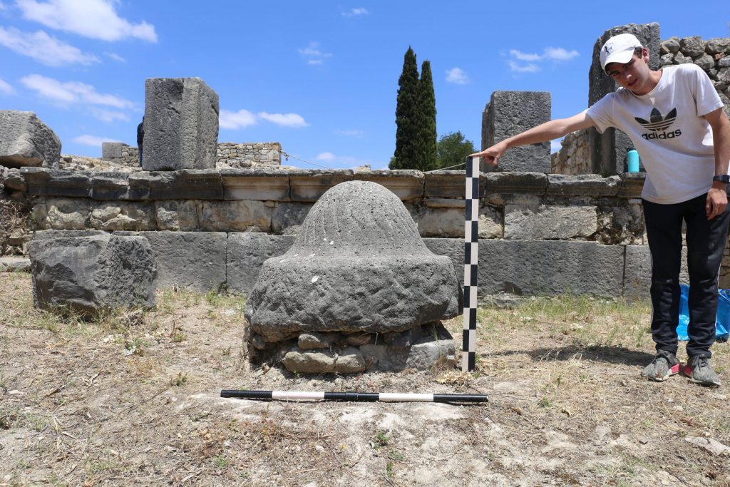 An olive millstone in Volubilis. Research assistant Drew Messing holds a tool for scale. Photo: Jared Benton.
