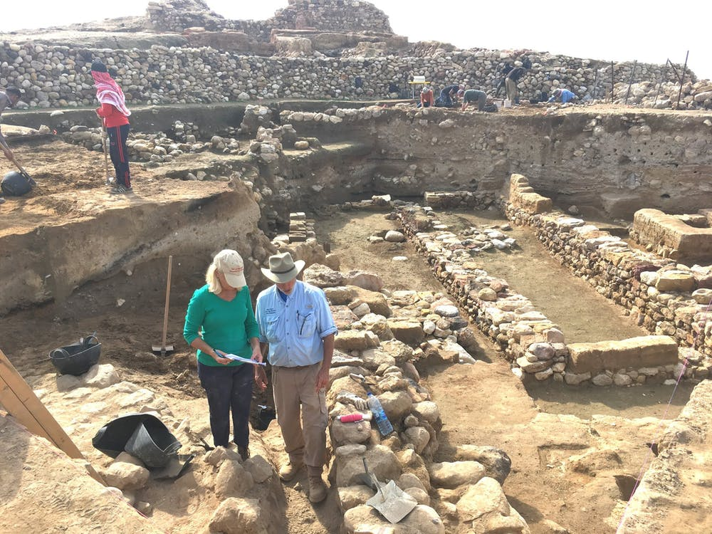 Researchers stand near the ruins of ancient walls, with the destruction layer about midway down each exposed wall. (Photo: Phil Silvia, CC BY-ND)